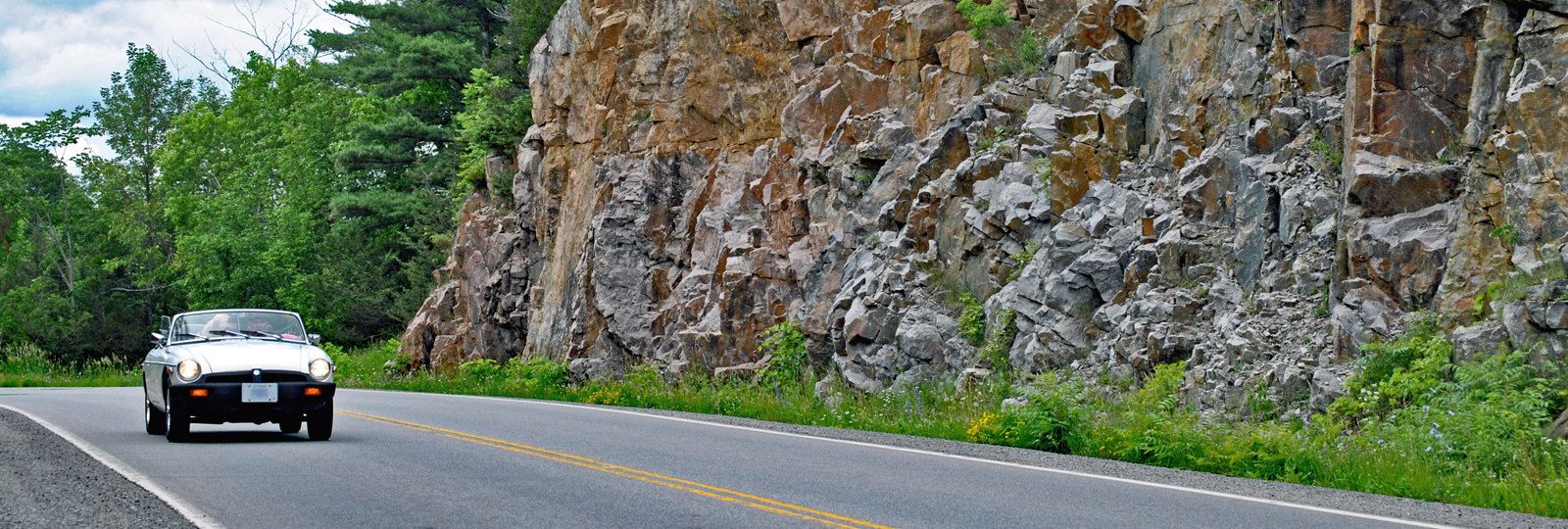 Car driving convertible beside rock cuts along the 1000 Islands Parkway