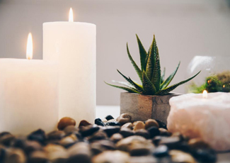 Lit candles, pebbles, and succulent plant.
