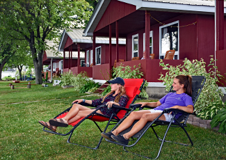 Women relaxing in lounge chairs outside a cabin