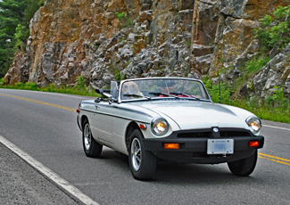 Convertible car being drove along side a rock-cut on the 1000 Islands Parkway